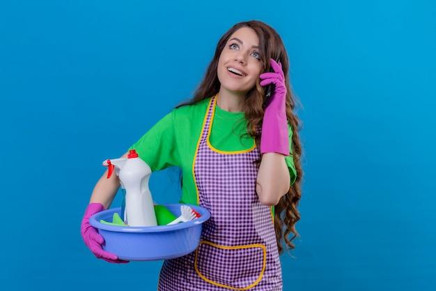 Vrouw, met, lang, golvend haar, vervelend, schort, en, rubberhandschoenen, vasthouden, bekken, met, schoonmaken, gereedschap, sprekend op mobiele telefoon, het glimlachen, met, blij gezicht, staand, op blauw