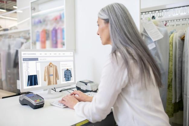 Vrouw met lang grijs haar achter stomerij receptie computer kijken met haar rug naar camera
