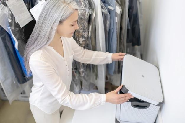 Vrouw met lang grijs haar in lichte kleren werken in de doos van de opening van de stomerij in de buurt van kledingrek