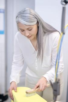 Vrouw met lang grijs haar in witte blouse die zich ijverig gebogen over het borstelen van kleren bevindt