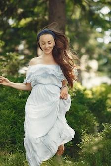 Vrouw met lang haar. dame in een blauwe jurk. meisje met ongerepte natuur.