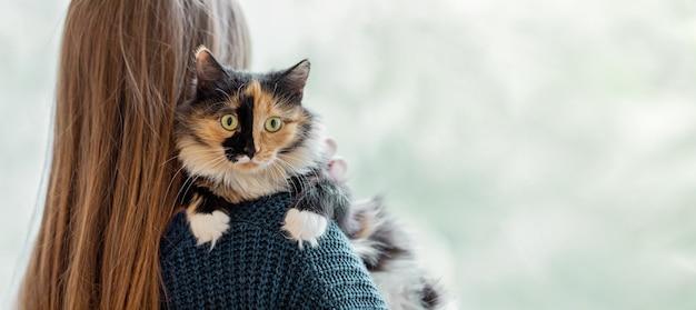Vrouw met lang haar dat haar schouder vasthoudt en haar huisdier tegen haar knuffelt - driekleurige jonge kat. achteraanzicht. favoriete huisdieren. selectieve aandacht.