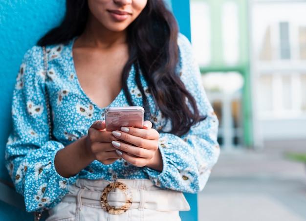 Vrouw met lang haar die haar telefoon met behulp van