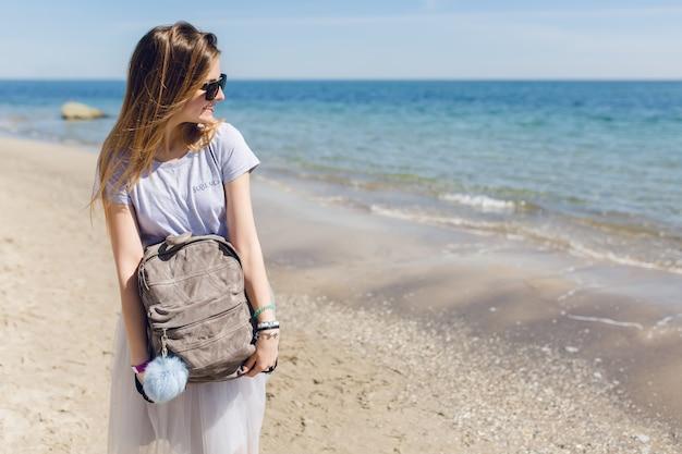 Vrouw met lang haar en tas in handen staat in de buurt van zee