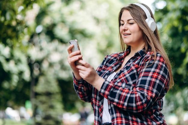 Vrouw met lang haar, in een geruit hemd, in een koptelefoon, met een smartphone in haar handen buitenshuis