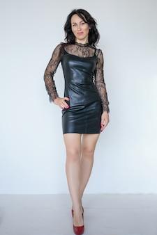 Vrouw met lang haar in een korte zwarte jurk en rode schoenen