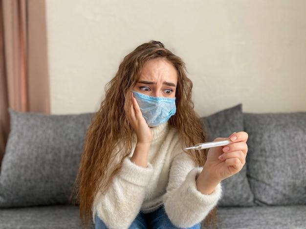 Vrouw met lang haar in een medisch masker en een thermometer in haar handen. de vrouw heeft koorts bij hoge temperatuur. pandemisch coronavirus