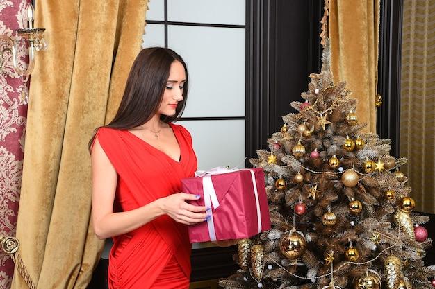 Vrouw met lang haar in rode jurk met huidige doos bij kerstboom thuis. nieuwjaar, kerstvakantie voorbereiding en viering. tweede kerstdag concept