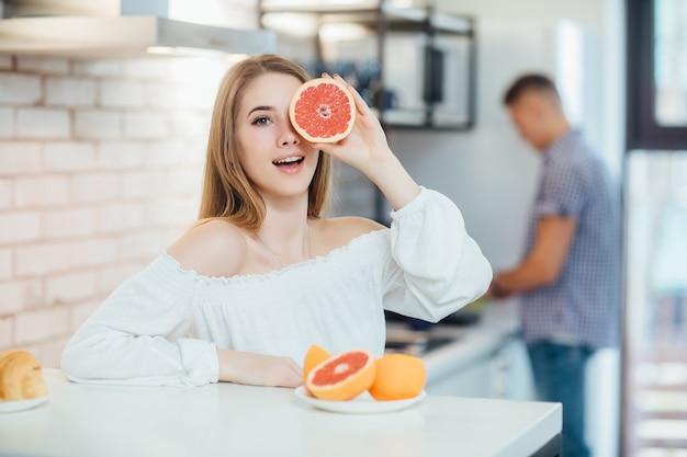 Vrouw met lang haar meisje kleurrijke ogen make-up vasthouden aan ogen grapefruit citrus