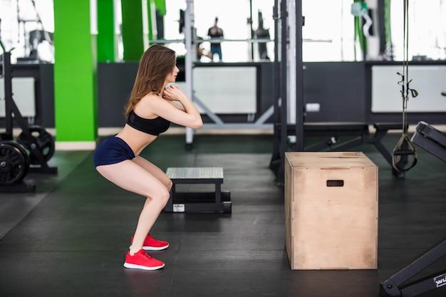 Vrouw met lang haar werkt met stap box sport simulator in fitnessruimte