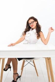 Vrouw met lang haar witte blouse. leraar met bril ziet er aantrekkelijk uit. verleidelijke kantoorbeheerder zit aan tafel. lady strikte leraar of verleidelijke officemanager. ze is blij om bezoeker uit te nodigen.