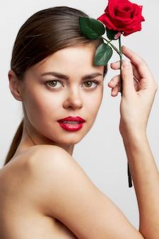 Vrouw met lang kapsel met een bloem in de buurt van het hoofd luxe spa-behandelingen bijgesneden weergave