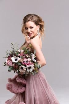 Vrouw met lang krullend haar in een roze jurk en bruiloft bloemen.
