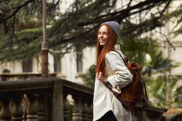 Vrouw met lang rood haar poseren en wandelen wandelen op de achtergrond van een oud gebouw historisch si...