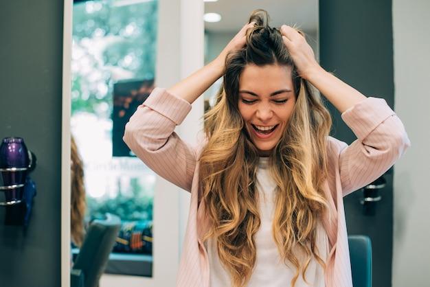 Vrouw met lange haarzitting in een kapper