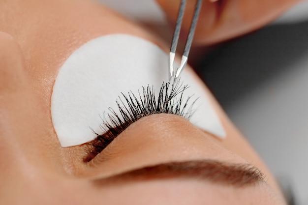 Vrouw met lange wimpers in de schoonheidssalon. wimpers extensie procedure close-up. cosmetica en make-up.