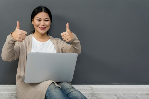 Vrouw met laptop die ok teken toont