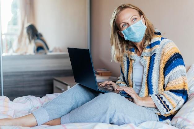 Vrouw met laptop en medisch masker in quarantaine thuis