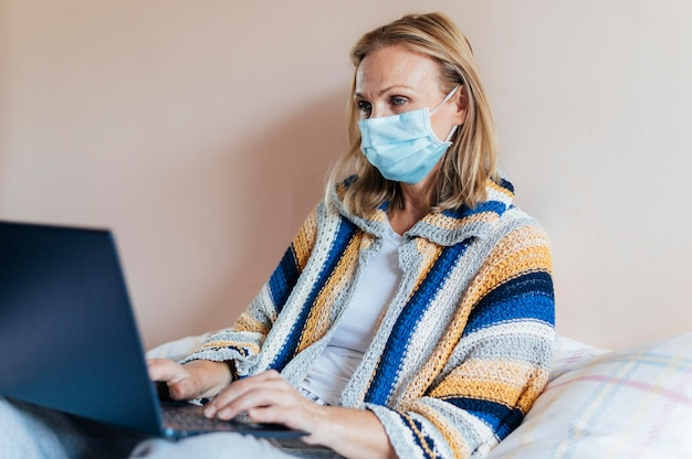 Vrouw met laptop en medisch masker in quarantaine
