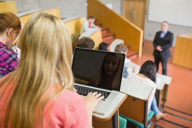 Vrouw met laptop met studenten en leraar bij collegezaal