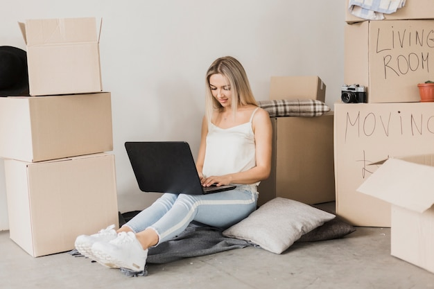 Vrouw met laptop omringd door kartondozen