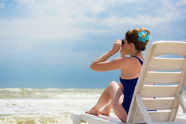 Vrouw met laptop op het strand kijkt in verrekijker