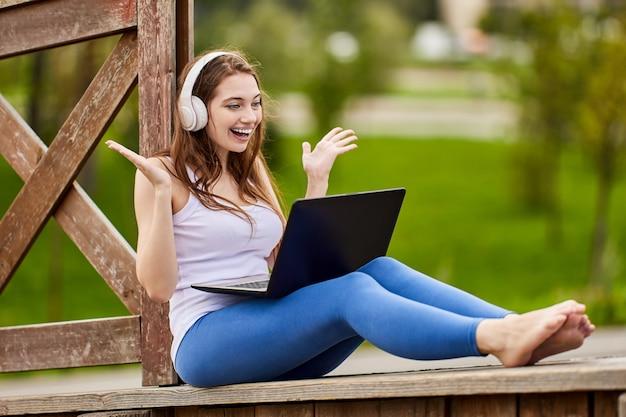 Vrouw met laptop reageert expressief terwijl ze naar het scherm kijkt