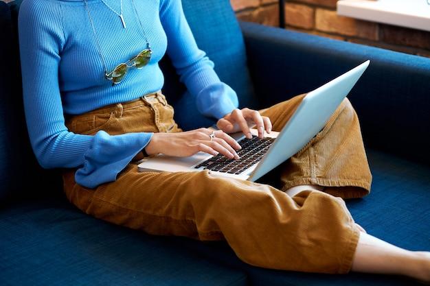 Vrouw met laptop thuis zittend op de bank