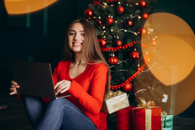 Vrouw met laptop zitten door kerstboom