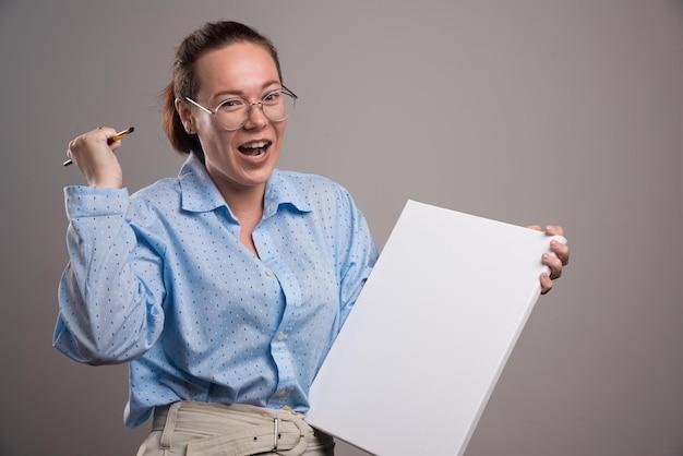 Vrouw met leeg canvas en penseel op grijs