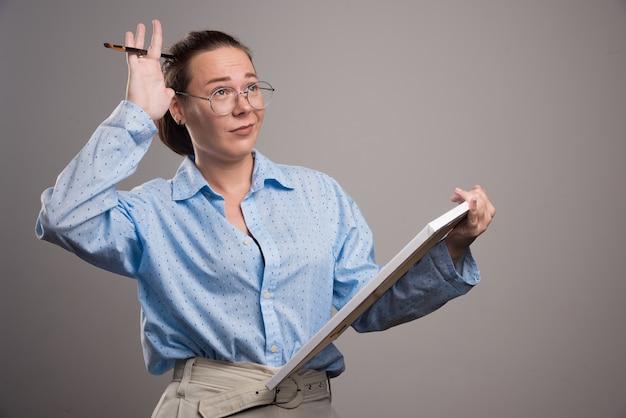 Vrouw met leeg canvas en penseel op grijze achtergrond