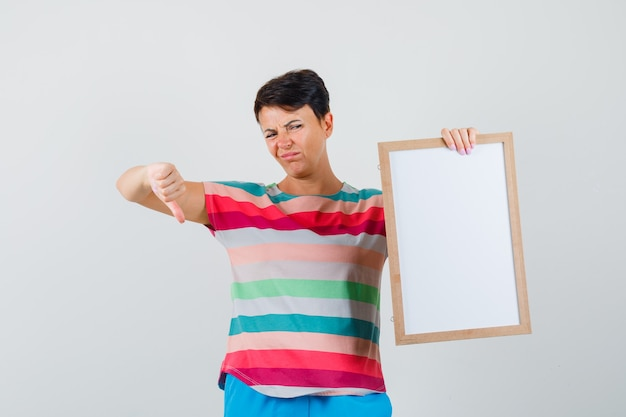 Vrouw met leeg frame, duim omlaag in gestreepte t-shirt, broek en op zoek naar ontevredenheid.