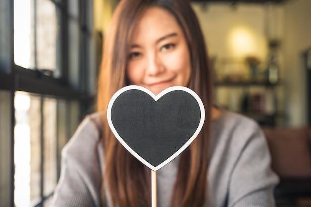 Vrouw met lege hart vorm schoolbord teken
