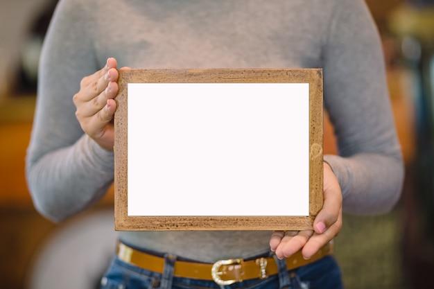 Vrouw met lege houten frame in koffie winkel