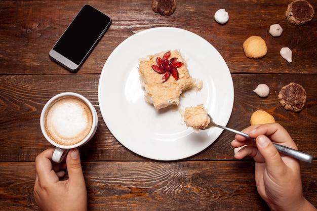Vrouw met lekker dessert en kopje koffie in café