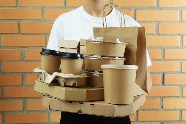 Vrouw met levering containers voor afhaalmaaltijden op bakstenen muur achtergrond