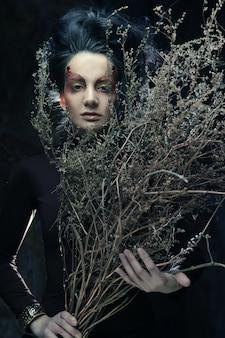 Vrouw met lichte make-up en droge takken