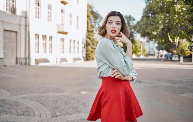 Vrouw met lichte make-up in een shirt en in een rode rok loopt in de zomer op straat in de buurt van het gebouw