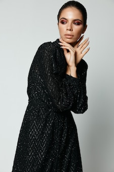Vrouw met lichte make-up in zwarte jurk op zoek naar de zijkant