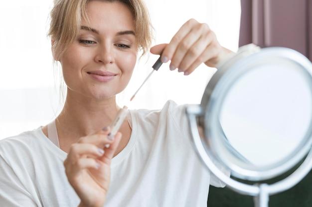 Vrouw met lipgloss en spiegel