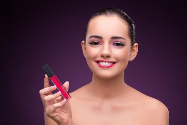 Vrouw met lippenstiftbuis in schoonheidsconcept