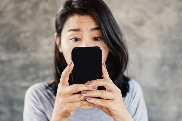 Vrouw met loensen kijken naar mobiele telefoon