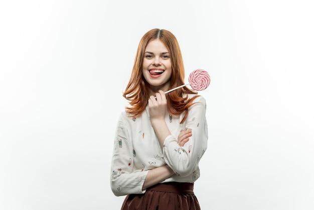 Vrouw met lolly snoep in haar tanden lichte achtergrond vreugde