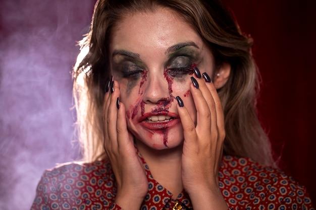 Vrouw met make-up als bloed dat haar hoofd vasthoudt
