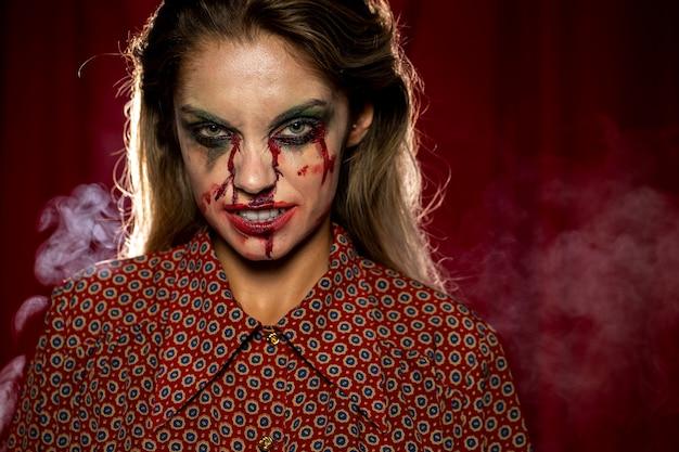 Vrouw met make-up als bloed grijnzen
