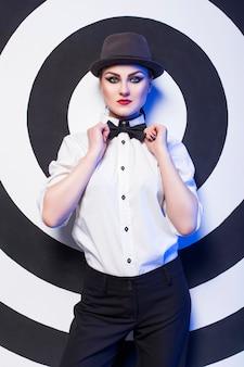 Vrouw met make-up die een wit overhemd en bowtie draagt