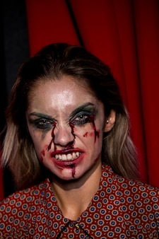 Vrouw met make-up die lijkt op bloed dat haar tanden toont