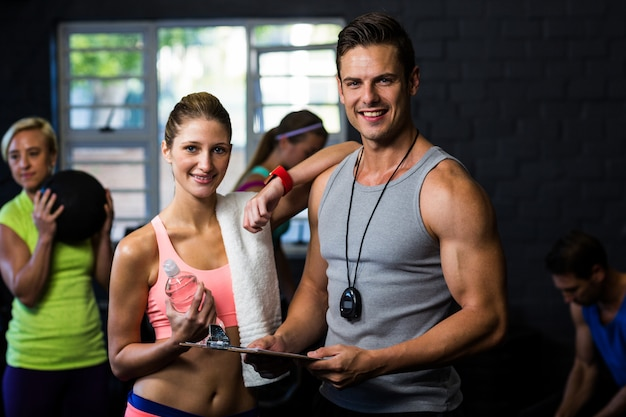 Vrouw met mannelijke trainer in de fitness-studio