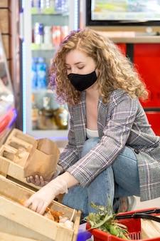 Vrouw met masker bij het winkelen kruidenierswinkel op de markt
