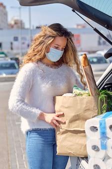 Vrouw met masker die boodschappentassen in de kofferbak stopt